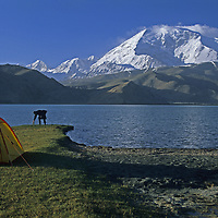 A trekker camps by Lake Karakul in the Pamir Mountains of Xinjiang province in far western China. Mustagh Ata background (24,750'). Mark Newcomb (MR)