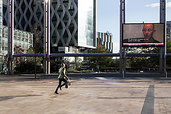 © Licensed to London News Pictures . 24/09/2014 . Media City , Salford , UK . A man runs for a tram . Autumn sunshine and big reflected light off the surface of glass buildings at Salford's Media City this morning as commuters travel to work  . Photo credit : Joel Goodman/LNP
