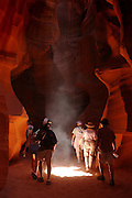 Tourists hike through Upper Antelope Canyon, which is located on Navajo Nation land near Page, Arizona. The slot canyon is a favorite stop for vacationers traveling the southwestern region of the United States.