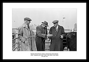 Salesman Richard Kenny watches a bargain being struck between Abbey Thompson and George Walker at the Dublin Cattle Market<br />
