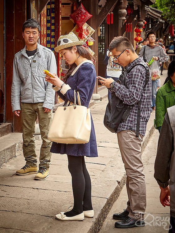 A Chinese student looks on enviously at his colleagues who are immersed in online conversations on their mobile phones