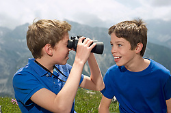Two teenage boys holding binoculars in Alps