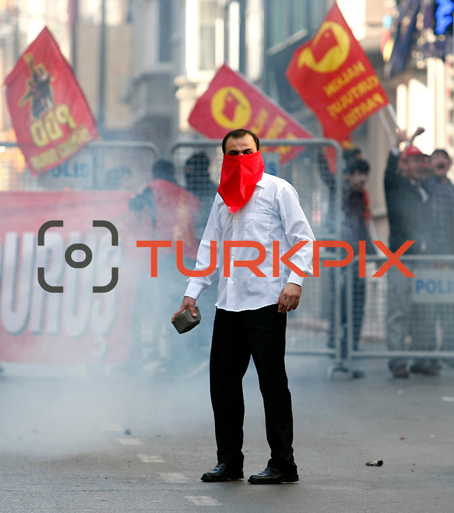 A masked protester throws a stone toward police as clashes erupt between police and protesters during May Day celebrations in Istanbul, Turkey, Wednesday May 1, 2013. Police fired tear gas to disperse hundreds of demonstrators trying to break through barricades to access Istanbul's Taksim Square which the government, citing security reasons, banned a rally on the square which is undergoing major renovations. May 1 demonstrations in Istanbul organized demonstrators clashed with police in protest against the government. Events, many demonstrators were injured, a large number of people affected by the tear gas used by police. Photo by AYKUT AKICI/TURKPIX