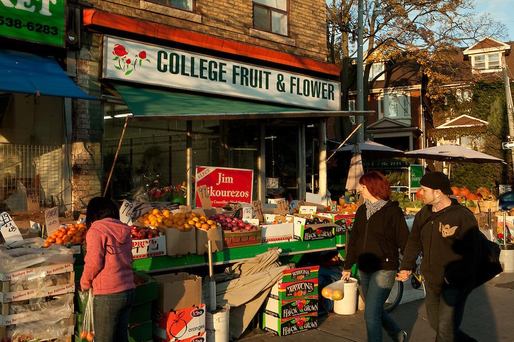 Strollers pass College Fruit & Flower on College Street in Toronto's Little Italy neighborhood.