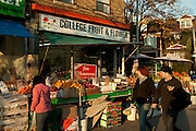 Strollers pass College Fruit & Flower on College Street in Toronto's Little Italy neighborhood.