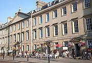 People sitting outside cafes on Georgian street of North Parade, Bath, Somerset, England, UK