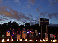 Goshen, New York - People stand on the track, which is lined with luminaria in remembrance of cancer victims, during the Relay for Life at Goshen High School on June 16, 2012. The Relay for Life is the American Cancer Society's signature fundraising event. Participants celebrate the lives of people who have battled cancer, remember loved ones lost, and fight back against the disease by raising money.