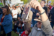 "Apr. 15, 2009 -- PHOENIX, AZ: A man holds up a copy of the US Constitution during the ""Tea Party"" at the Arizona State Capitol in Phoenix Wednesday. Nearly 10,000 people attended the rally, which was supposed to be in opposition to the Obama economic plan but turned into a general anti-Obama rally.  Photo by Jack Kurtz"