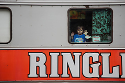 """The children of Brazilian actor Paulo dos Santos peek out of their train car during a stop. Ringling Bros. and Barnum & Bailey Circus started in 1919 when the circus created by James Anthony Bailey and P. T. Barnum merged with the Ringling Brothers Circus. Currently, the circus maintains two circus train-based shows, the Blue Tour and the Red Tour, as well as the truck-based Gold Tour. Each train is a mile long with roughly 60 cars: 40 passenger cars and 20 freight. Each train presents a different """"edition"""" of the show, using a numbering scheme that dates back to circus origins in 1871 — the first year of P.T. Barnum's show."""