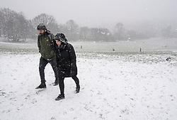 © Licensed to London News Pictures. 24/01/2021. London, UK. A coupe battle through heavy Snowfall on Hampstead Heath in Hampstead in north London. Parts of the UK continue to suffer from flooding caused by Storm Christoph. Photo credit: Ben Cawthra/LNP