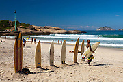 Line of surfboards in the sand, with surf instructor in front of them carrying surf board. Ipanema beach, Rio de Janeiro.