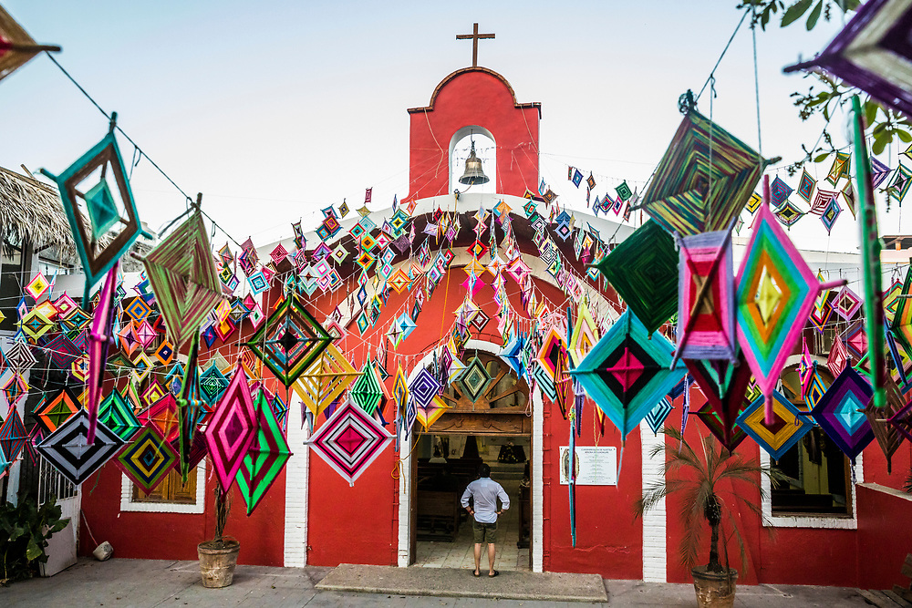 """The main church in Sayulita, Nayarit, Mexico decorated outside with Ojo de Dios or """"God's Eye"""", a local symbol and craft of the indigenous Huichol culture."""