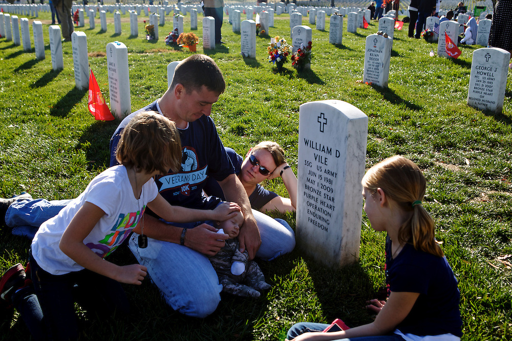 ARLINGTON, VA - NOVEMBER 11: Jim Finnegan (L), his wife Carolyn and their children, Colleen, 7, Erin, 9, and William, 2 months, sit before the grave of Finnegan's best friend, Staff Sgt. William Vile who died in the war in Afghanistan in 2009, on Veteran's Day at Arlington National Cemetery on November 11, 2012 in Arlington, Virginia. Finnegan named his son after his friend who he had known since he was 14 years old.