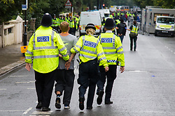 London, August 31st 2015. The day doesn't end well for one young man as police lead him in handcuffs towards their vans as revellers ignore the inclement weather to enjoy day two of the Notting Hill Carnival.