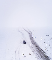 Aerial view of a car driving on a frozen road in the Blizzard in Rohukula, Estonia.