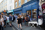Dolphin Arcade antique market at Portobello Road Market in Notting Hill, West London, England, United Kingdom. People enjoying a sunny day out hanging out at the famous Sunday market, when the antique stalls line the street.  Portobello Market is the worlds largest antiques market with over 1,000 dealers selling every kind of antique and collectible. Visitors flock from all over the world to walk along one of Londons best loved streets.