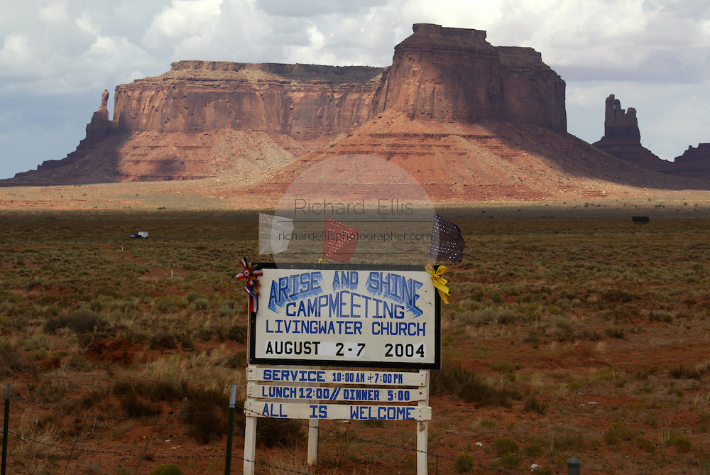 A sign advertising evangelical church meeting in Monument Valley on the southern border of Utah with northern Arizona. The valley lies within the range of the Navajo Nation Reservation. The Navajo name for the valley is Tsé Bii' Ndzisgaii - Valley of the Rocks.