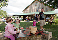 Audrey Manning and Abigail Dutton each pull up a crate and enjoy a game of checkers at the Beans and Greens Harvest Fest on Sunday afternoon.  (Karen Bobotas/for the Laconia Daily Sun)