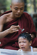 Young novice Monk having his head shaven and crying