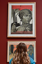 "© Licensed to London News Pictures. 07/11/2017. London, UK.  A student from Thomas Tallis School, Kidbrooke, south London, views ""Emancipated Woman:  Build Socialism!"", 1926, by Adolf Strakhov, one of several Soviet political propaganda displayed at the preview of ""Red Star Over Russia: A Revolution in Visual Culture 1905-55"" at Tate Modern.  The exhibition marks the centenary of the October Revolution and presents the visual history of Russia and the Soviet Union with works drawn from the late graphic designer David King. Photo credit: Stephen Chung/LNP"