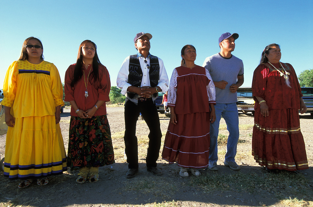 Members of an Apache girl's family  (two sisters, father, mother, brother and her grandmother) dance during her Sunrise Dance, a first menstruation rite, on the San Carlos Apache Indian Reservation in Arizona, USA. The women are dressed in camp dresses. The Sunrise Dance is held during the summer, within one year after the girl has had her first menstruation, and lasts for four days. The ceremony is an enactment of the Apache creation myth and during the rites the girl 'becomes' Changing Woman, a mythical female figure, and comes into possession of her healing powers. The rites are supposed to prepare the girl for adulthood and to give her a long and healthy life without material wants.