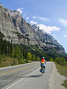A bicycle on the Icefields Parkway near Saskatchewan Crossing (5000 feet elevation) rides by spectacular peaks exceeding 10,000 feet elevation in Banff National Park, Alberta, Canada. This is part of the Canadian Rocky Mountain Parks World Heritage Site declared by UNESCO in 1984.