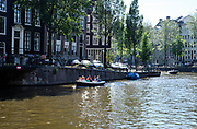 In summertime people having fun with theirs boats in the canals of Amsterdam, Netherlands.
