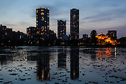 Bentendo temple illuminated at night stands in front of appartment building towers in Shinobazu Pond, Ueno Park, Ueno, Tokyo, Japan. Sunday May 8th 2016