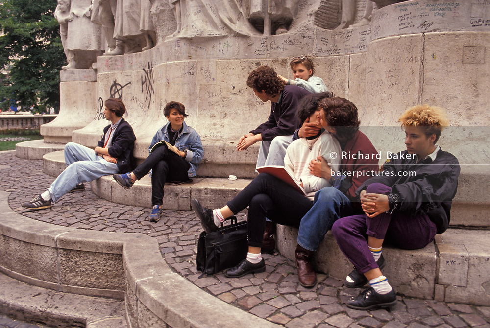 Young Hungarians socialise and kiss beneath a Soviet-era memorial, on 18th June 1990, in Budapest, Hungary.