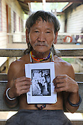 August 2012: Penan native, Maleng, holds a picture of his brother Sinan, who is deceased. This is the first photograph he ever had of his brother. Long Napir, Limbang district, Sarawak, Borneo<br /> <br /> The Limbang valley including Long Napir, a cluster of four settlements of Penan and Kelabit people, is threatened by a new hydro-electric project which will flood the entire area, displacing thousands of native people. The Murum Hydro-electric project already underway affecting the Rejang region, will displace over 24,000 Dayak native residents, destroying their longhouses and forest habitat. The dam site is located on the Murum River, in the uppermost part of the Rajang River basin, 200km from Bintulu. Sarawak's primary rainforests have been systematically logged over decades, threatening the sustainable lifestyle of its indigenous peoples who relied on nomadic hunter-gathering and rotational slash & burn cultivation of small areas of forest to survive. Now only a few areas of pristine rainforest remain; for the Dayaks and Penan this spells disaster, a rapidly disappearing way of life, forced re-settlement, many becoming wage-slaves. Large and medium size tree trunks have been sawn down and dragged out by bulldozers, leaving destruction in their midst, and for the most part a primary rainforest ecosystem beyond repair. Nowadays palm oil plantations and hydro-electric dam projects cover hundreds of thousands of hectares of what was the world's oldest rainforest ecosystem which had some of the highest rates of flora and fauna endemism, species found there and nowhere else on Earth, and this deforestation has done irreparable ecological damage to that region.