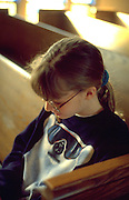 Girl age 10 sitting alone in church pew praying.  WesternSprings  Illinois USA