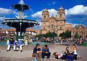 Young people gather in Plaza de Armas  square by the fountain in Cuzco in front of La Compania church in the ancient capital of the Inca Empire, Peru, South America