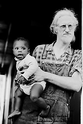A white man holds his black son in his arms.