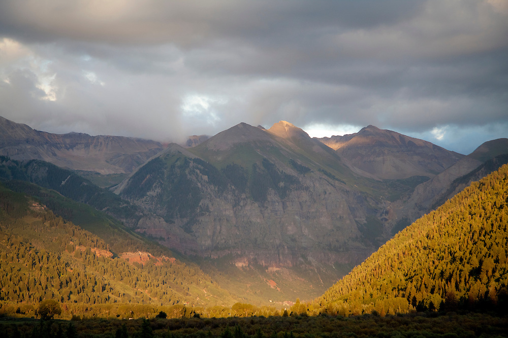 Evening light makes the Telluride Valley Floor glow under clouds from a passing front.