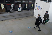 Socially distanced bus passengers wear face coverings while waiting for the next service, and the famous scientists who studied at University College London (UCL), on the Strand in central London, on 8th March 2021, in London, England. King's College London is a public research university located in London, United Kingdom, and a founding college and member institution of the federal University of London.