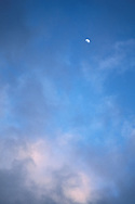 Moon and cumulus cloud, and pink light in deep blue evening sky at sunset.