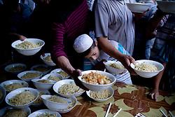 Uyghur men receive free meal at mosque before the break of  Ramadan in Hotan, Xinjian province in China.