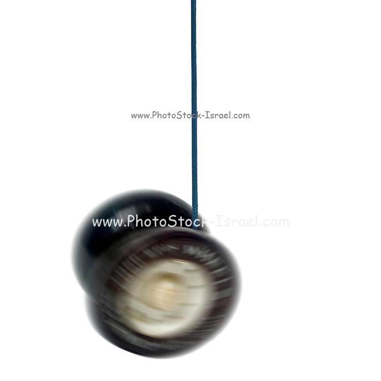 Digitally enhanced image of a spinning black and white yoyo on white background