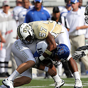 Memphis quarterback Taylor Reed (16) gets tackled by Central Florida long snapper Patrick McKiernan (57) during an NCAA football game between the Memphis Tigers and the Central Florida Knights at Bright House Networks Stadium on Saturday, October 29, 2011 in Orlando, Florida. (AP Photo/Alex Menendez)