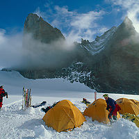 An expedition to climb Rakekniven spire (L) works in their base camp in the Filchner Mountains, Queen Maud Land, Antarctica.