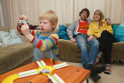White family, boy playing with toys.