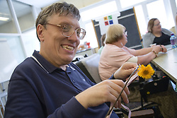 Woman enjoying a natural arts and crafts session run by Groundworks day centre,