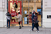 People wearing face masks walk past a lingerie shop along Oxford Street which is largely empty of shoppers as the national coronavirus lockdown three continues on 28th January 2021 in London, United Kingdom. Following the surge in cases over the Winter including a new UK variant of Covid-19, this nationwide lockdown advises all citizens to follow the message to stay at home, protect the NHS and save lives.
