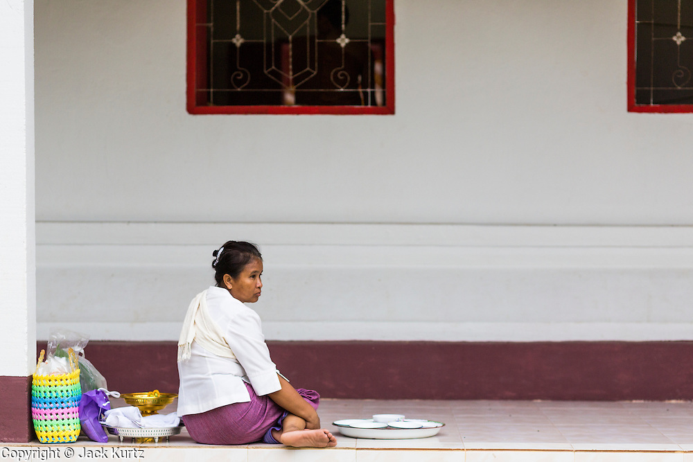 """29 JUNE 2014 - DAN SAI, LOEI, THAILAND:  A woman sits on the balcony around Wat Ponchai during the """"Ghost Festival."""" Phi Ta Khon (also spelled Pee Ta Khon) is the Ghost Festival. Over three days, the town's residents invite protection from Phra U-pakut, the spirit that lives in the Mun River, which runs through Dan Sai. People in the town and surrounding villages wear costumes made of patchwork and ornate masks and are thought be ghosts who were awoken from the dead when Vessantra Jataka (one of the Buddhas) came out of the forest. On the last day of the festival people participate in merit making ceremonies at the Wat Ponchai in Dan Sai and lead processions through town soliciting donations for the temple.    PHOTO BY JACK KURTZ"""