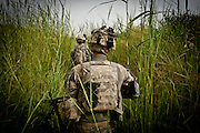 An American soldier makes his way through head-high grass laced with improvised explosive devices, or IEDs, just outside the walls of Combat Outpost Nolen.