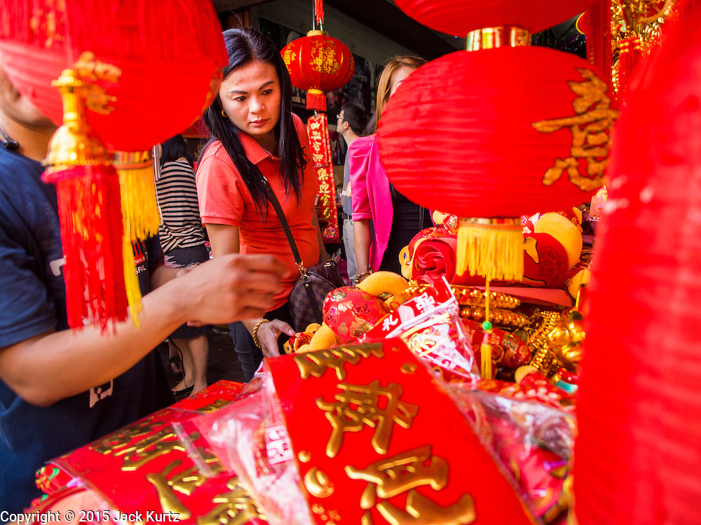 """17 FEBRUARY 2015 - BANGKOK, THAILAND:  People shop for Chinese New Year decorations on Yaowarat Road in Bangkok's Chinatown. Chinese New Year is February 19 in 2015. It marks the beginning of the Year of Sheep. The Sheep is the eighth sign in Chinese astrology and the number """"8"""" is considered to be a very lucky number. It symbolizes wisdom, fortune and prosperity. Ethnic Chinese make up nearly 15% of the Thai population. Chinese New Year (also called Tet or Lunar New Year) is widely celebrated in Thailand, especially in urban areas like Bangkok, Chiang Mai and Hat Yai that have large Chinese populations.      PHOTO BY JACK KURTZ"""