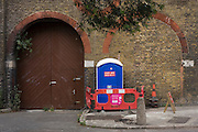 A Portaloo is closed off near railway arches in a central London street