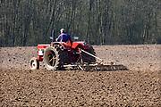 Nederland, Kekerdom, 22-3-2019 Een boer, loonwerker, rijdt met een tractor, trekker, over een akker, het land, Foto: Flip Franssen