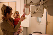 Young girl of two undergoes a chest x-ray Mother helps child relax