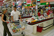 Marzena Sobczynska, her husband Hubert, and daughter Klaudia finish the family's grocery shopping for one weeks' worth of food at the Auchan hypermarket. The huge new supermarket, ten minutes' drive from their home, is near a big intersection that serves four or five other bedroom communities. (Supporting image from the project Hungry Planet: What the World Eats.)